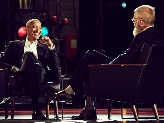 Former President Obama, left, speaks to David Letterman
