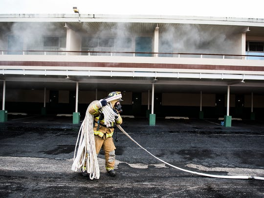 A firefighter packs up a hose while Gettysburg Fire Department conducts training with Adams County fire departments at a vacant motel building on Steinwehr Avenue.