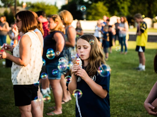 Cayden Windisch, 9, of Littlestown, blows bubbles Saturday June 25, 2016 at Alloway Creek Intermediate School in Littlestown during a vigil and memorial service for Codie Powell.