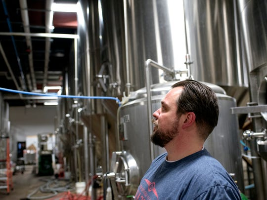 Old Nation Brewing Company's Travis Fritts oversees fermentation tanks full of M-43 beer on Wednesday, Feb. 28, 2018, in Williamston.