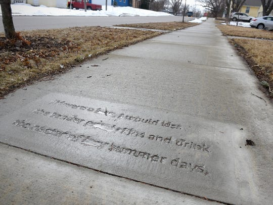 A verse is written into a sidewalk near Wilson Avenue