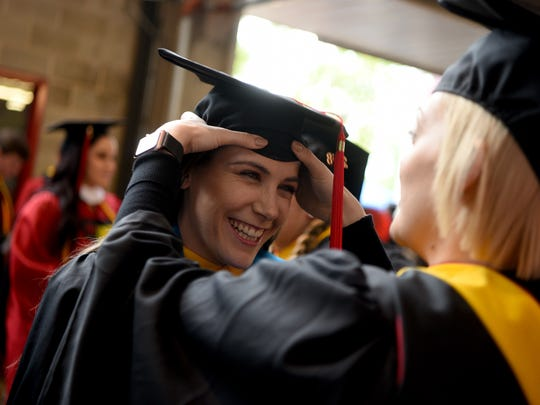 The 252nd commencement of Rutgers University was held at High Point Solutions Stadium in Piscataway on Sunday, May 13, 2018. Brittany Gleeson of Plainsboro, gets help with her cap from friend and fellow graduate Megan McCarthy of Sayreville.