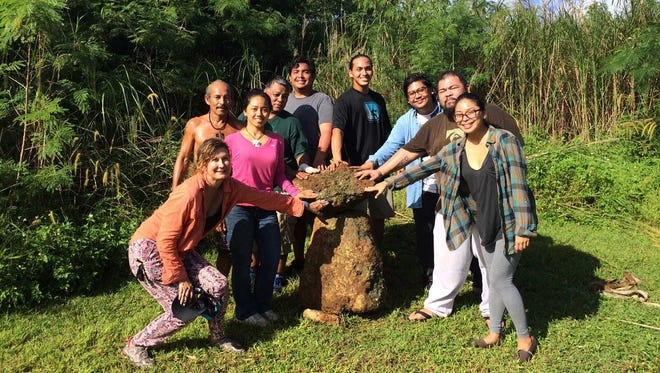 From left to right: Dr. Kelly Marsh-Taitano, Tammy Manglona, Joe Viloria, Luke Duenas, Beau Mesa, Daniel Stone, Jr., Nathan Topasna, Jerome Eclevea and Francine Fujihara pose with a tasa and haligi they finished quarrying from the jungle area at the Sagan Kotturan Chamoru Cultural Center in Tumon.