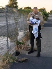 This Friday, Nov. 27, 2015 photo, provided by the Los Angeles County Sheriff's Department shows an unidentified deputy holding an infant girl where she was found abandoned under asphalt and rubble, left, near a bike path in Compton, Calif.