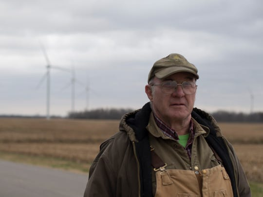 Duane Sickels poses for a photo in front of a wind