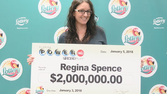 Pensacola resident Regina Spence poses with a $2 million check from Florida Lottery on behalf of herself and her colleagues.