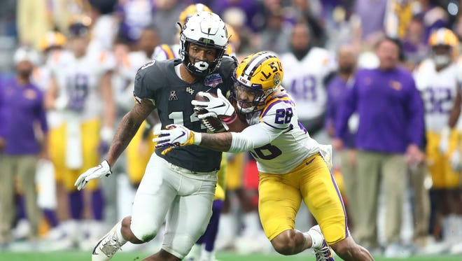 UCF wide receiver Gabriel Davis, left, is hit by LSU Tigers cornerback Mannie Netherly in the second quarter of the 2019 Fiesta Bowl at State Farm Stadium in Glendale, Ariz.