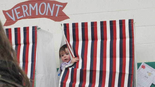 Francesca Montague, aged 14 months, of Huntington, views Town Meeting Day proceedings while her father, Larry Montague, casts votes behind a curtain.