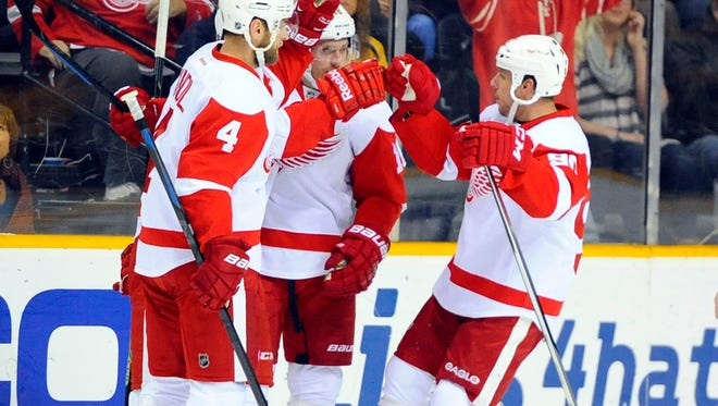 Detroit Red Wings players celebrate after a goal during the first period against the Nashville Predators at Bridgestone Arena.