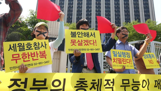 South Korean protesters shout slogans and hold placards reading 'Total incompetence of the government for sluggish response' and show red cards during a rally against government's health policy in Seoul, South Korea, 04 June 2015.