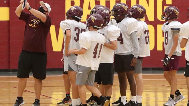 Drew Turner, co-offensive coordinator and offensive line coach, calls a play Monday during a practice of the Walsh Jesuit High School football team at the school in Cuyahoga Falls.