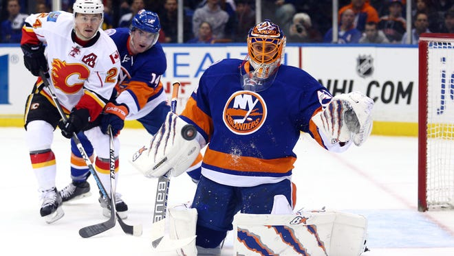 Jaroslav Halak makes a save in front of Flames left wing Jiri Hudler and teammate Thomas Hickey.