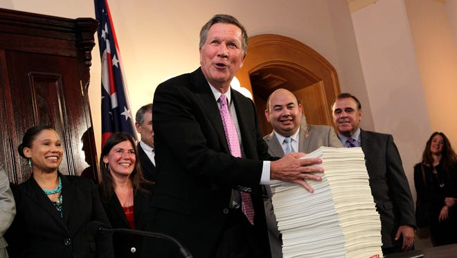"""Gov. John Kasich presents Ohio's 2016-2017 operating budget after signing it Tuesday in Columbus. Kasich said the $71.2 billion, 2-year state budget helps people without getting """"loose"""" with spending."""