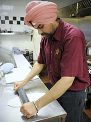 Kam Sidhu rolls out a flatbread to make naan in a tandoor