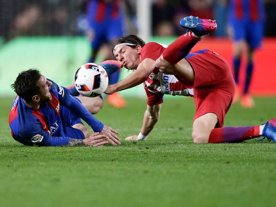 Barcelona's Lionel Messi falls after a foul from Atletico's Filipe Luis, right, during the the Copa del Rey semifinal second leg soccer match between FC Barcelona and Atletico Madrid at the Camp Nou stadium in Barcelona, Spain, Tuesday Feb. 7, 2017. (AP Photo/Manu Fernandez)