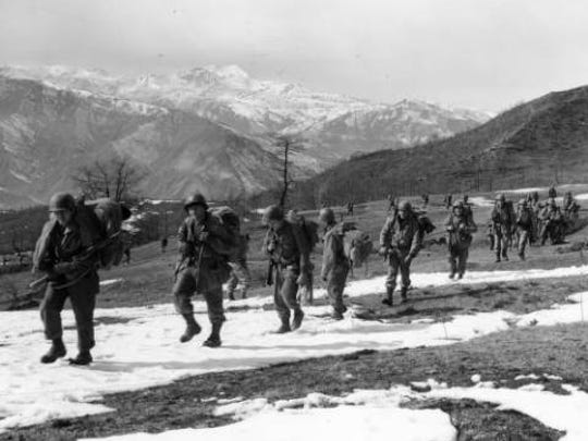 A line of Tenth Mountain Division soldiers climb up a ridge wearing helmets, combat fatigues, large knapsacks during the Italian Campaign. According to the caption the peak of Mount Belvedere rises in the distance.