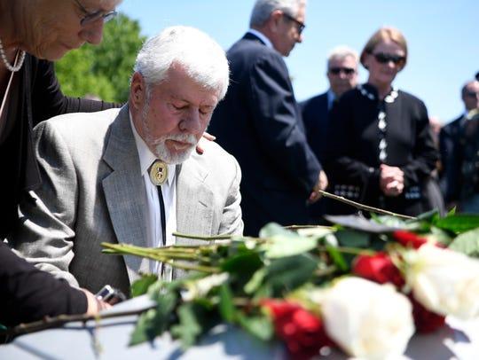 Gary Bain says a prayer over Ryan's casket on Wednesday.