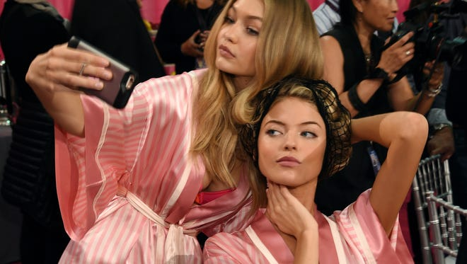 Gigi Hadid (L) and Martha Hunt are seen backstage before the 2015 Victoria's Secret Fashion Show at Lexington Avenue Armory.