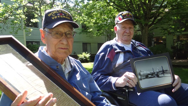 Miles Abel, left, and Jim Farrens show off contraband they brought home from World War II. Abel has a copy of Gen. Douglas MacArthur's surrender instructions to the Japanese emperor, and Farrens has a photograph of the Enola Gay, which dropped the atomic bomb on Hiroshima.