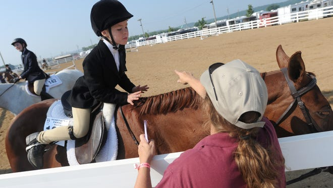 Becky Henkel, with Deerfield Happy Helpers 4-H Club, discusses with her mom, Susan Henkel, the course for the crossrails competition at Monday morning's Jr. Fair Horse Show at the Ross County Fair.