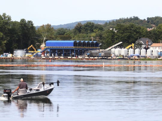The Pompton Lake cleanup project proceeds in the background as a boater motors across the lake.