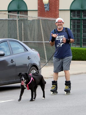 Rollerblader James Pledger uses dog power provided by Luna to cruise along Rogers Avenue, Tuesday, June 2, 2020, during a spin in downtown Fort Smith.