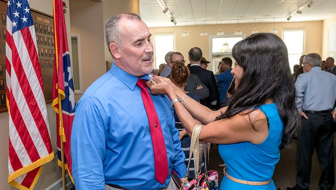 Graduating senior Joe Stout is pinned by Tennessee Department of Veterans Affairs Commissioner Many Bears Grinder after a ceremony at Middle Tennessee State University.