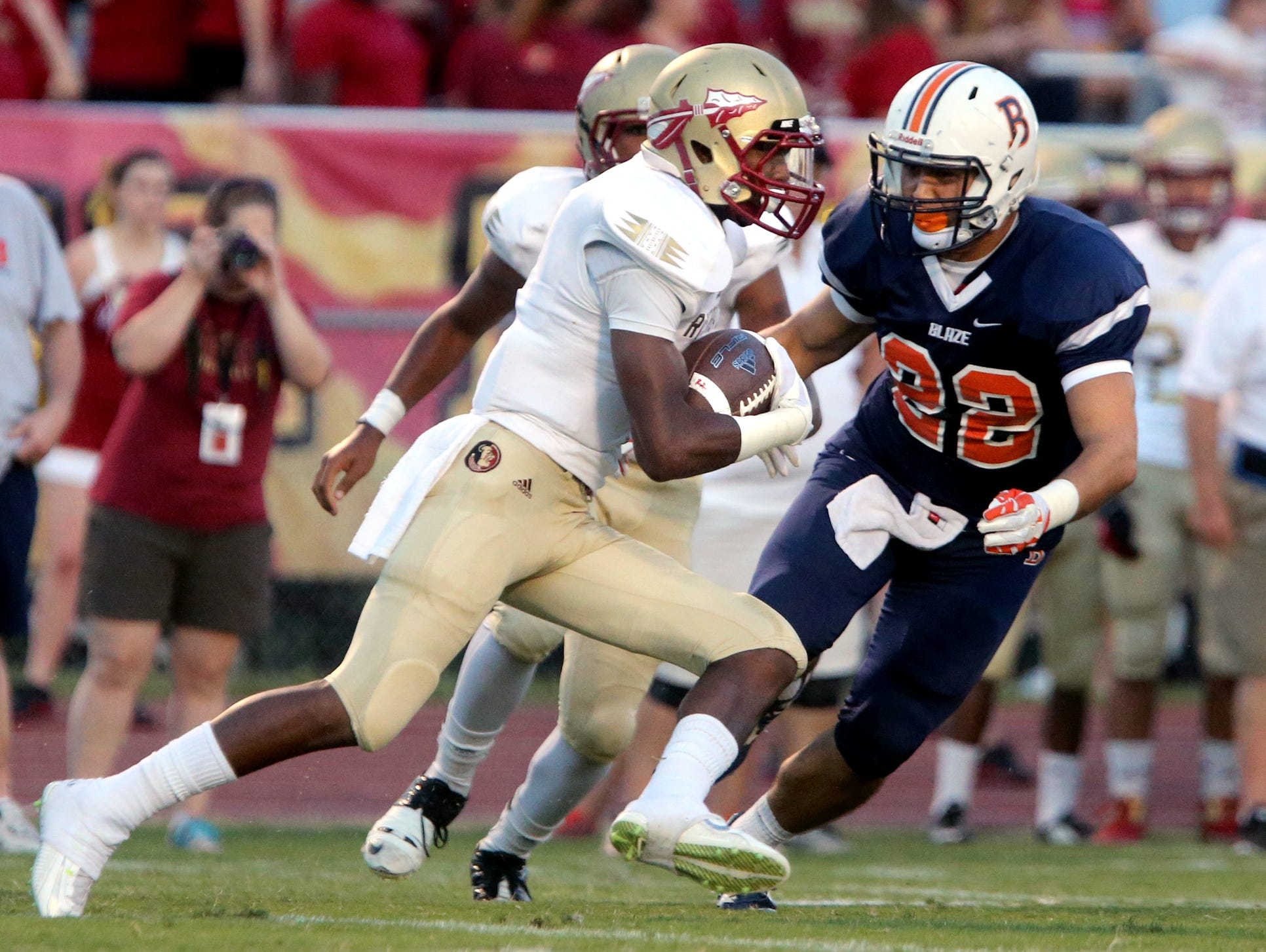 Riverdale's Marquise Cantrell (4) runs the ball as Blackman's Tony Ochoa (22) moves in for the tackle, at Blackman, on Friday Sept. 4, 2015.