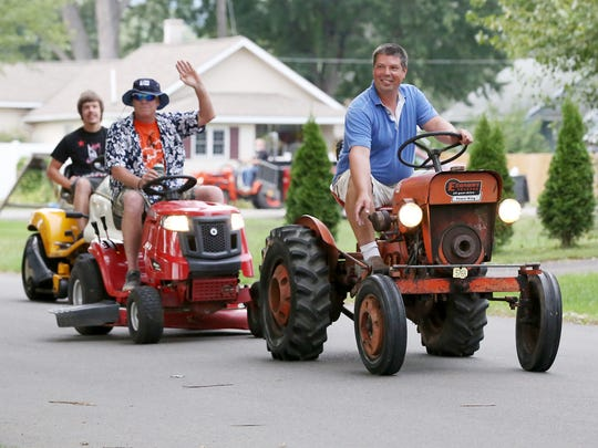 Gene Woodford leads the pack of tractors on Florence Street in Elmira, in rememberance of Kent Kramer.