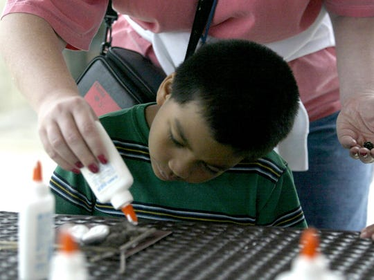 Angel Rodriguez of West Des Moines got help with an art project from is teacher, Jane Wirth, during a Metro Arts Alliance event in 2004 at Raccoon River Park Nature Lodge.
