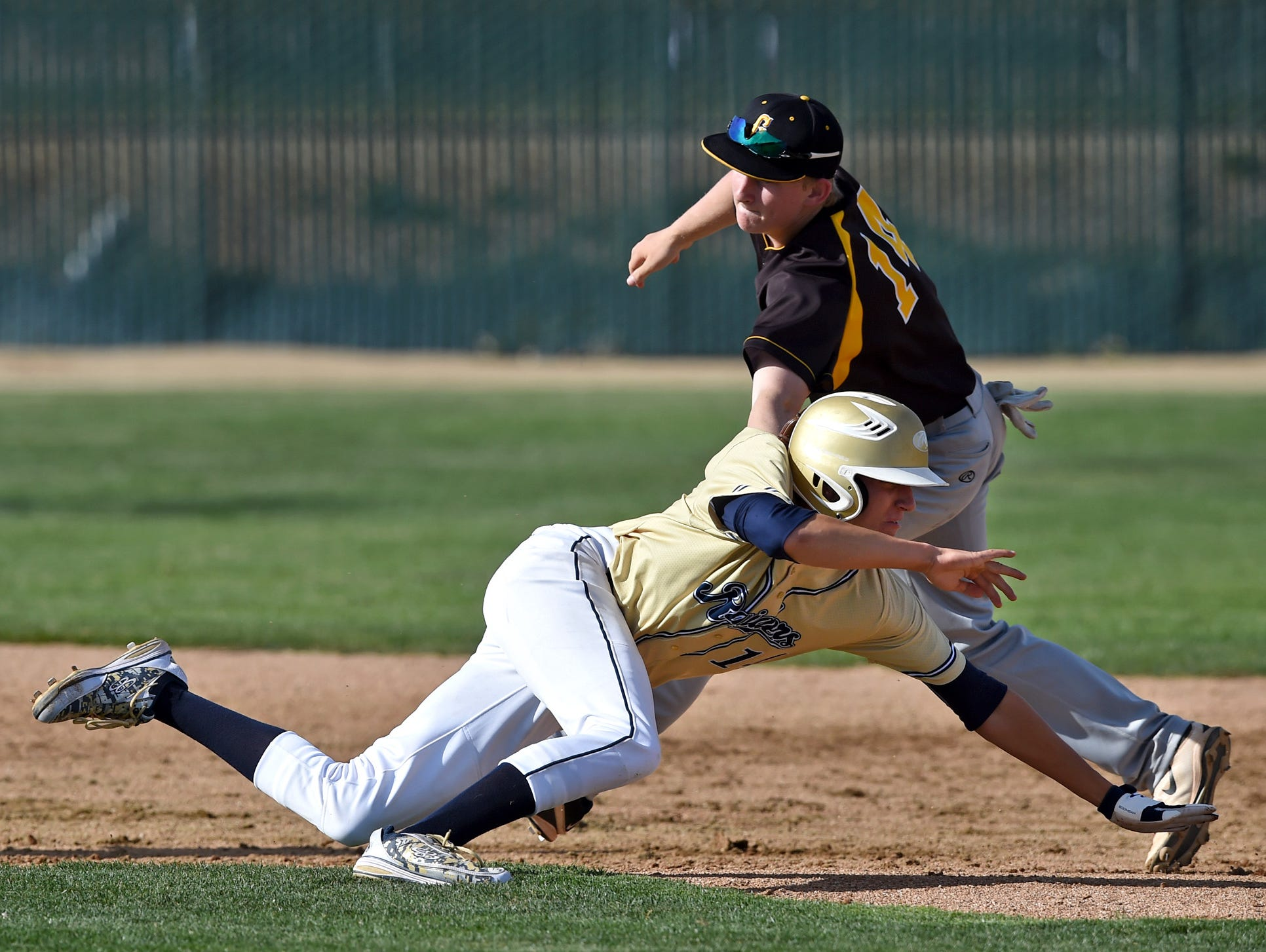 Galena's Andrew West reaches to tag Reed's Levi Sanchez who was caught in a rundown between second and third base during Tuesdays game at Reed.