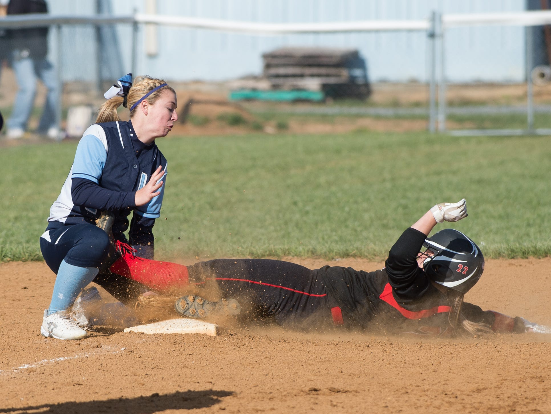 Lake Forest's Faith Garey (2) tags out Red Lion's Kaylee Hazewski (22) at third base.