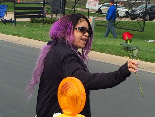 Tyka Nelson holds a rose outside Paisley Park, the