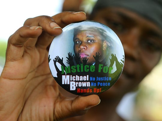 Nikki Jones holds a button in support of Michael Brown while visiting the community near where he was fatally shot in Ferguson.
