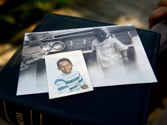 A school picture of a 10-year-old Michael Harris sits with one when he was five lying on top of a family picture album that his mother, Betty Harris, has Aug. 17 in Lansing.