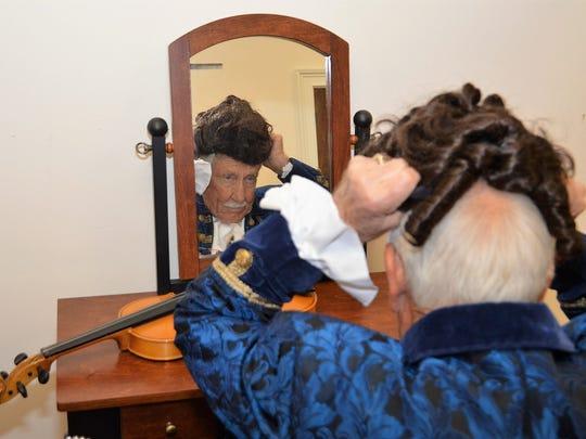 "Tony Buckun putting on wig to portray President John Adams in ""Mr. President."""
