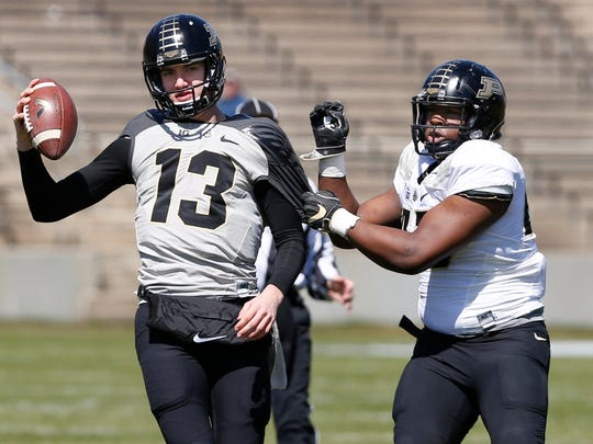 Jeff Marks, right, of the Defense sacks quarterback Jack Plummer of the Offense during the Purdue spring game Saturday, April 7, 2018, at Ross-Ade Stadium. The Offense defeated the Defense 42-36.