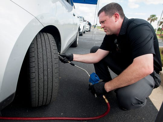 Aronn Walters checks tires as he helps Hyundai performs