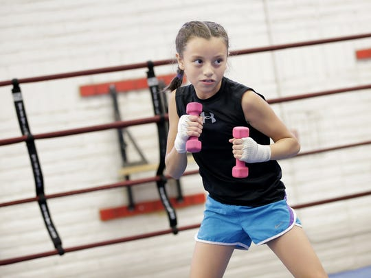 Nine-year-old Ivy Enriquez does some weighted shadow boxing at the Carolina Recreation Center.