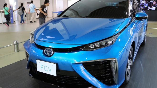 A visitor looks at Toyota Motor's new fuel cell vehicle on display last month at the company's showroom in Tokyo.
