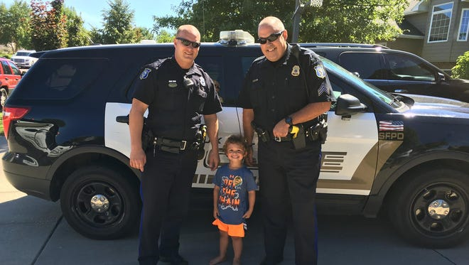 Asher, 4, poses with Officer Beltman and Sgt. Forster at his birthday party on Sunday.