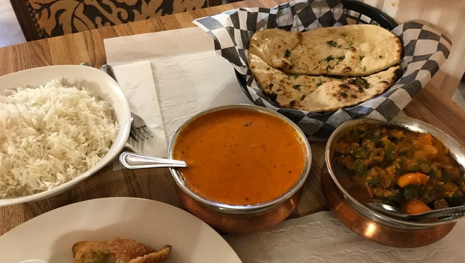 Some of the dishes on the menu at Spicy India include, clockwise from top right, garlic naan bread, okra masala, samosa with mint sauce and basmati rice. Butter chicken is in the center. Pictured on Feb. 27, 2018.