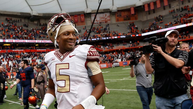 Florida State quarterback Jameis Winston smiles as he walks off the field after his team's 38-20 win over Syracuse in an NCAA college football game, Saturday, Oct. 11, 2014, in Syracuse, N.Y. (AP Photo/Mike Groll)