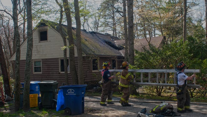 Fire fighters carry a ladder at the scene of a home fire on Mohawk Trail in Medford Lakes.