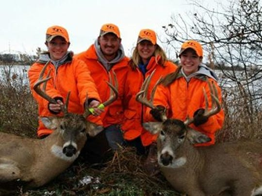 Cayley Vande Berg (far left) and her twin sister Cassidy (far right) pose with their parents, Chad and Tammy, as they display the bucks they shot on the first day of hunting season.