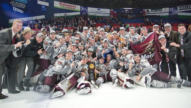 The Norwich University men's hockey team celebrates its 4-1 NCAA championship victory over Trinity in Utica, N.Y., on Saturday night.