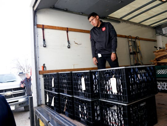 Salvation Army warehouse driver Joshua Ben helps load creates containing meat donated by Tommy Bolack into a truck on Wednesday at San Juan Meats in Kirtland.