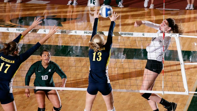 Michigan State's Brooke Kranda, right, hits over Michigan's Katherine Mahlke (13) and Abby Cole (17) to finish off Michigan on match point Wednesday, Sept. 30, 2015, in East Lansing, Mich. Watching at left is MSU's Abby Monson (10). MSU won 3-0.