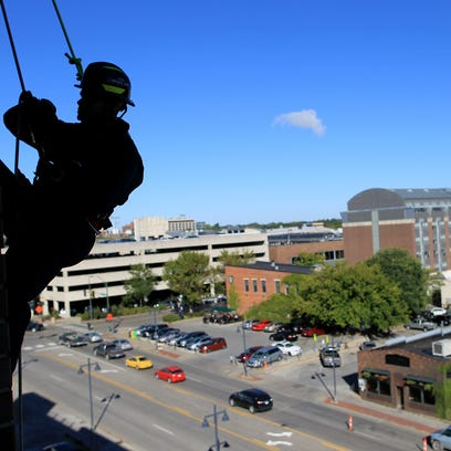 Iowa City firefighter Jason Jordan rappels down the