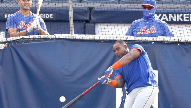New York Mets Michael Conforto (left) watches as Yoenis Cespedes takes batting practice in the cage before Sunday's exhibition game against the New York Yankees at Yankee Stadium in New York.
